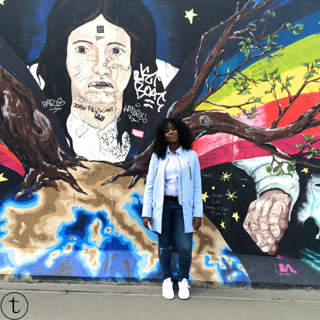 at the berlin wall in germany wearing blue coat and ripped jeans from zara